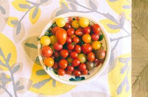 Schüssel Tomaten auf bedrucktem Stoff foto