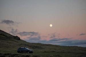 Auto auf Grasfeld bei Sonnenuntergang geparkt foto