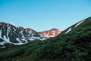 Sonnenlicht auf schneebedeckten Bergen foto