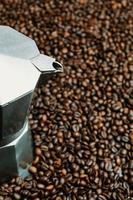 Stahltopf umgeben von Kaffeekörnern