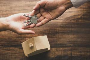 Draufsicht des Immobilienmaklers, der dem Kunden Schlüssel gibt