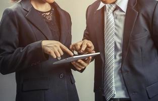 zwei Geschäftsleute, die auf Tablette zeigen foto