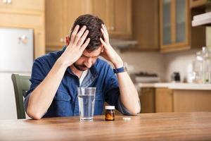 junger Mann mit Kopfschmerzen foto