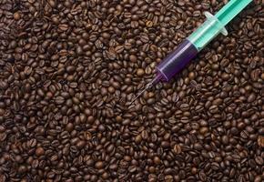 Spritze mit giftiger Flüssigkeit auf Kaffeebohnen foto
