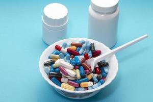 verschiedene Pillen auf einem Teller und zwei weiße Flaschen