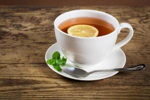 Tasse Tee mit Minzblatt und Zitrone foto