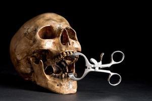 Schädel mit Zahnarztzange foto
