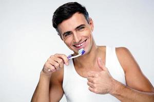 glücklicher Mann, der seine Zähne putzt foto