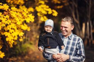 Großvater hält sein Enkelkind am Arm, Herbst foto