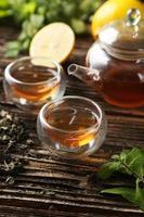 Tasse mit grünem Tee und Teekanne auf braunem hölzernem Hintergrund foto