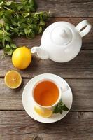 Tasse mit grünem Tee und Teekanne auf grauem hölzernem Hintergrund foto