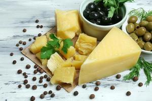 Parmesankäse, frische Kräuter und Oliven auf hölzernem Hintergrund