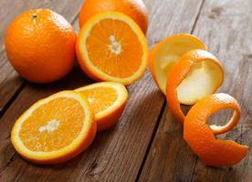 Orangen und getrocknete Schale auf einem ländlichen Tisch foto