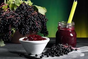 Holunder-Marmelade auf grauem Tischgrünhintergrund