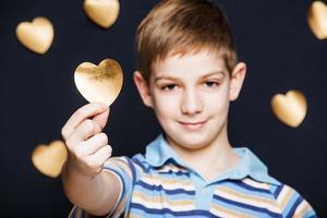 Porträt des Jungen, der goldenes Herz auf dunklem Hintergrund hält foto
