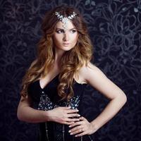 schönes Mädchen mit langen braunen gekräuselten Haaren, dunkler Hintergrund foto