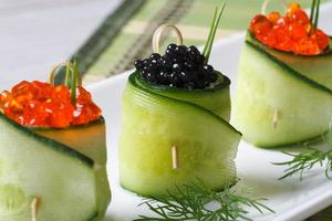 Gurkenröllchen gefüllt mit rotem und schwarzem Kaviar foto