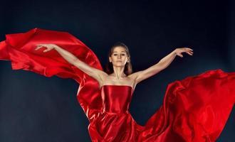 schöne inspirierende Frau, die in einem roten Seidenkleid fliegt, das fliegt foto