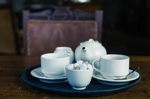 Teekanne, Tasse und Zucker auf Tablett foto