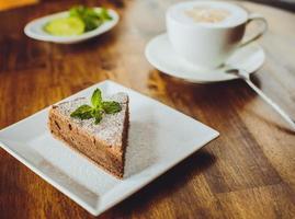 Schokoladenkuchen mit einem Cappuccino auf einem Holztisch in einem Restaurant foto