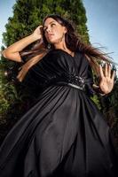Außenporträt des schönen Mädchens im langen schwarzen Luxuskleid.
