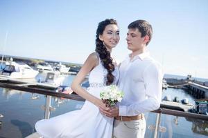 Braut und Bräutigam auf dem Hintergrund des Yachtclubs, jung foto