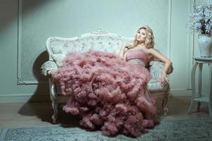 Mädchen in einem prächtigen Kleid sitzt auf dem Sofa. foto