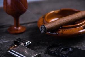 kubanische Zigarre im Aschenbecher mit Feuerzeug und Cutter