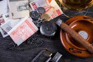 kubanisches Domino-Spiel auf dem Tisch mit Zigarre, Rum, Pessonoten