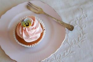 hausgemachte rosa Zuckerguss Vanille Cupcakes mit essbaren Blumen foto