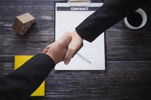 zwei Personen geben sich die Hand über einen Vertrag