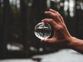 Hand hält eine Glaskugel foto