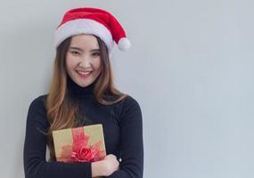 Frau hält Geschenk mit Weihnachtsmütze foto