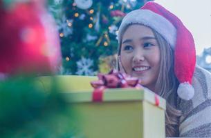 Frau lächelt in der Nähe von Weihnachtsgeschenk