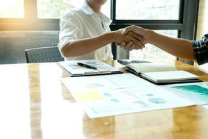 Profis schütteln sich die Hände über einen Schreibtisch