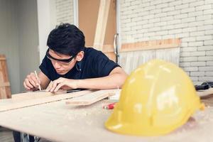 Zimmermann Mann arbeitet Holz Holzbearbeitung in Schreinerei Ladenhaus, Handwerker misst Holzrahmen für Holzmöbel in der Werkstatt. Verarbeitungs- und Berufskonzept foto