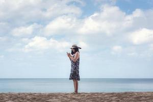 Porträt der asiatischen Frau mit Handy gegen blauen Himmel