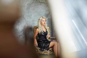 glamouröse Blondine sitzt auf einem Stuhl im Innenraum foto