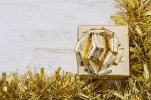 goldene Geschenkbox auf weißem Tisch.