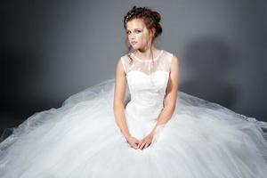 erstaunliches Brauthochzeitskleid, das auf dem froor sitzt. Studioaufnahme foto