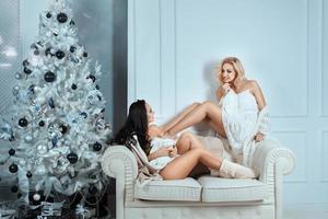 zwei Mädchen sitzen auf der Couch und unterhalten sich zu Hause. foto