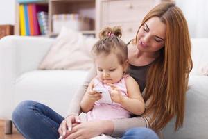 Fokus niedlichen kleinen Mädchen lernen mit dem Handy foto