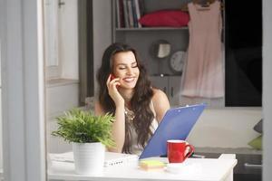 schöne Geschäftsfrau, die zu Hause arbeitet foto