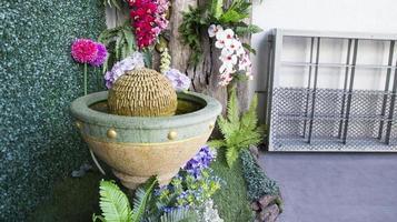 bunte gefälschte Blume, die mit dem Brunnen verziert