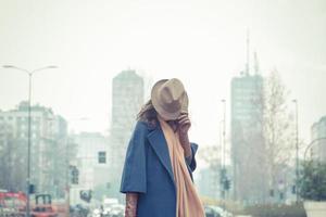 schöne junge Brünette posiert in den Straßen der Stadt foto