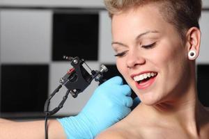 schöne Frau schaut, wie jemand ein Tattoo macht foto