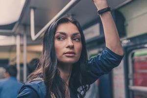 schönes Mädchen, das in einem U-Bahnwagen aufwirft foto
