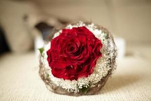 Hochzeitsstrauß mit roten Rosen, die auf einem Bett liegen