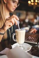 Geschäftsfrau in Gläsern mit Laptop träumt im Restaurant foto