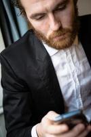 hübscher Hipster eleganter Mann auf dem Handy foto